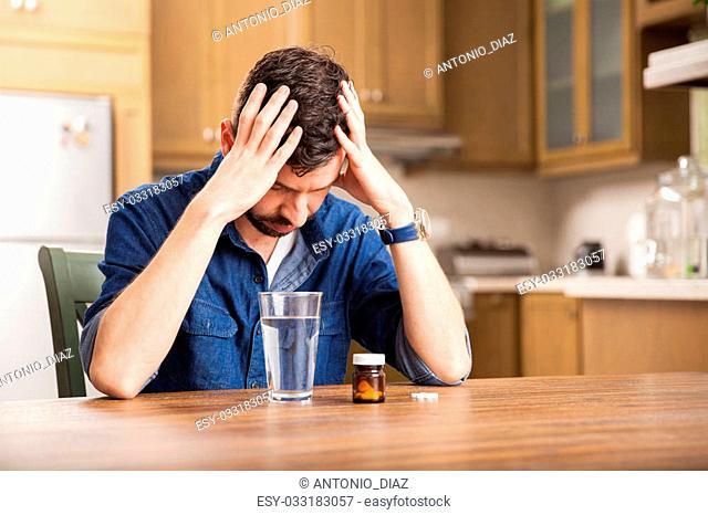 Guy with a beard and a denim shirt holding his head in his hands while having a headache at home