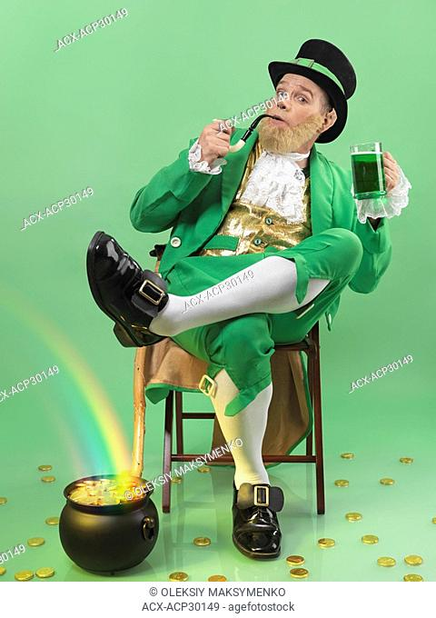 Leprechaun in bright green clothes holding a smoking pipe and a beer mug with a rainbow coming from a pot full of gold. Isolated on white background