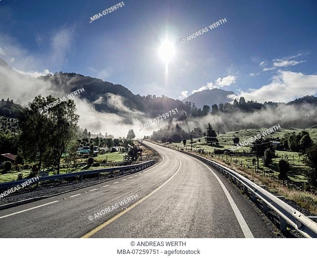 Carretera Austral south of Lago Yelcho, sun over morning haze, paved road in backlit, meadows, Patagonia, Chile