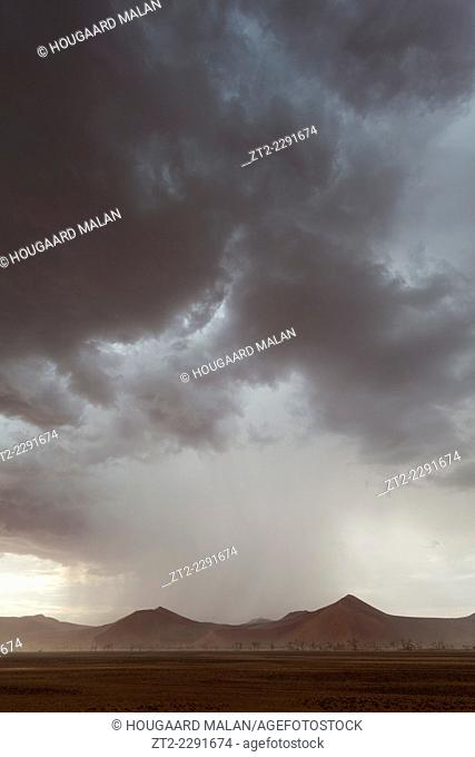 Landscape photo of a big rainstorm over the dunes of Sossusvlei. Sossusvlei, Namib Naukluft National Park, Namibia