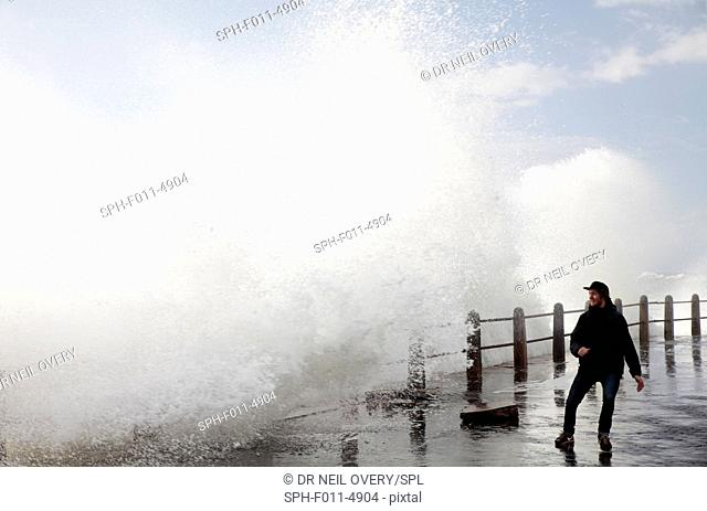 Man walking along sea front with crashing waves, Sea Point, Cape Town, Western Cape, South Africa