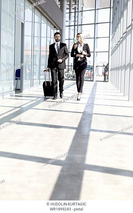 Business partners walking in lobby at airport