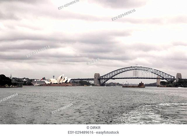 Skyline of Sydney with the Sydney Opera House and Sydney Harbour Bridge on a cloudy day
