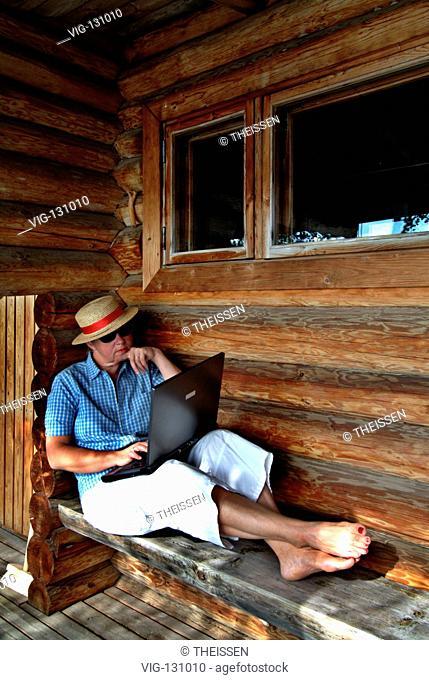 MR PR Frau sitzt auf Terasse von einem Sauna H³tte am See in Finnland und arbeitet mit einem Notebook / MR PR woman working with a notebook sitting on veranda...