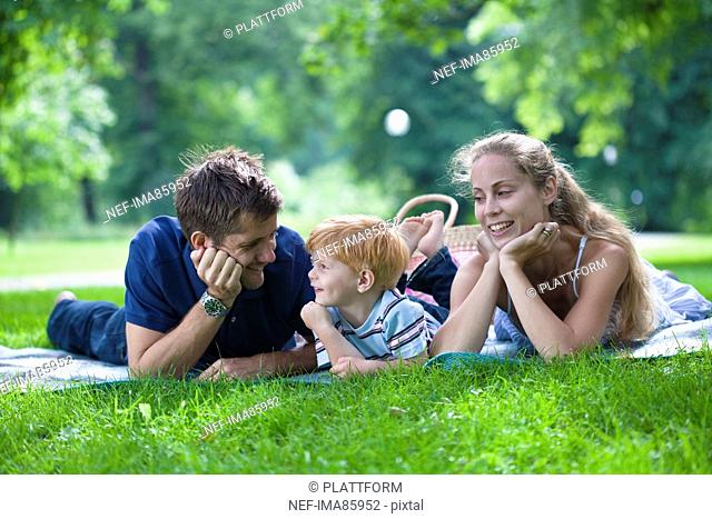 Parents with son lying in park and looking away
