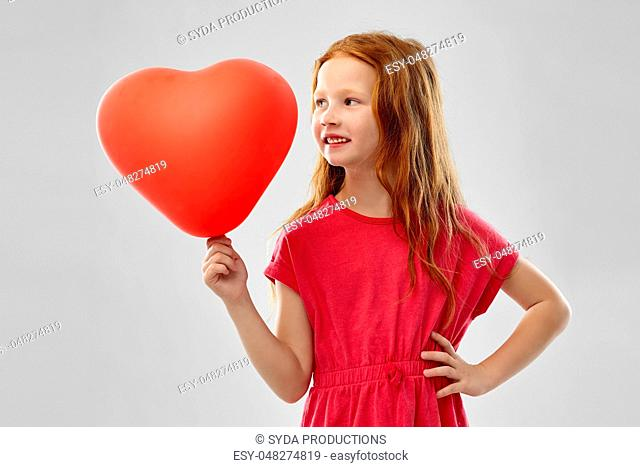 smiling red haired girl with heart shaped balloon