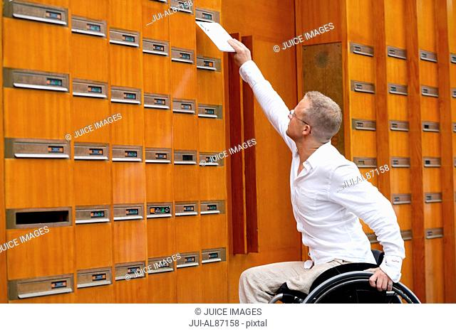Male amputee in wheelchair reaching for mailbox