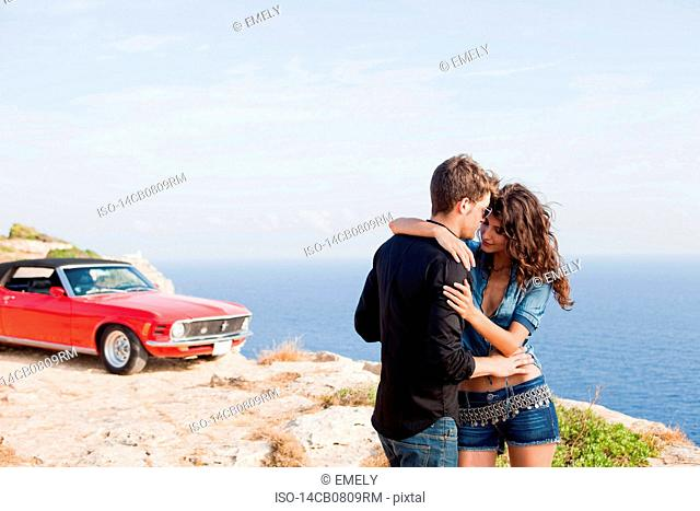 couple standing at cliff in front of car
