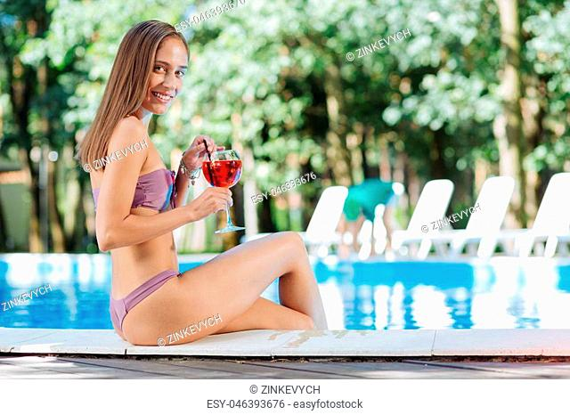 Cocktail near pool. Beautiful businesswoman drinking summer refreshing cocktail while sitting near pool