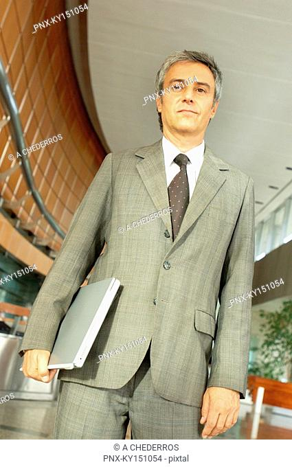 Mature businessman standing and holding file, low angle view