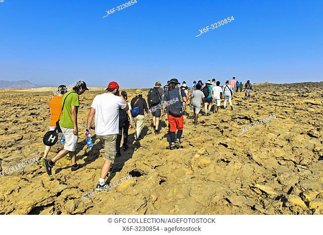 Overtourism, groups of tourists on the way to the Dallol caldera, one of the most inhospitable and barren place on earth, geothermal field of Dallol