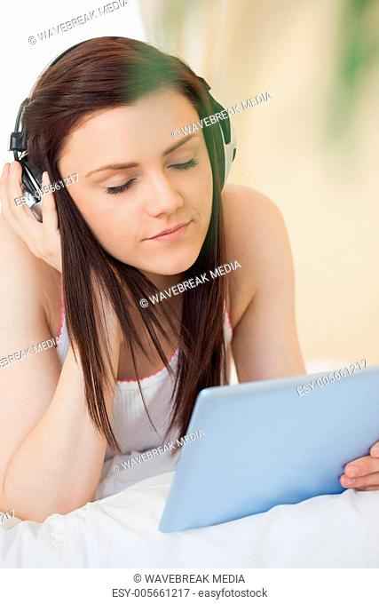 Relaxed girl listening to music and using a tablet pc lying on a bed