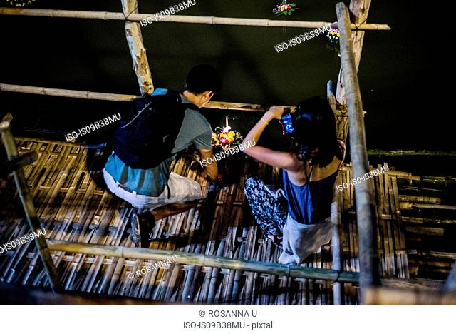 Young man and woman by Ping River in Chiang Mai during Loy Krathong Lantern Festival, releasing floating lantern down the Ping River, Chiang Mai, Thailand