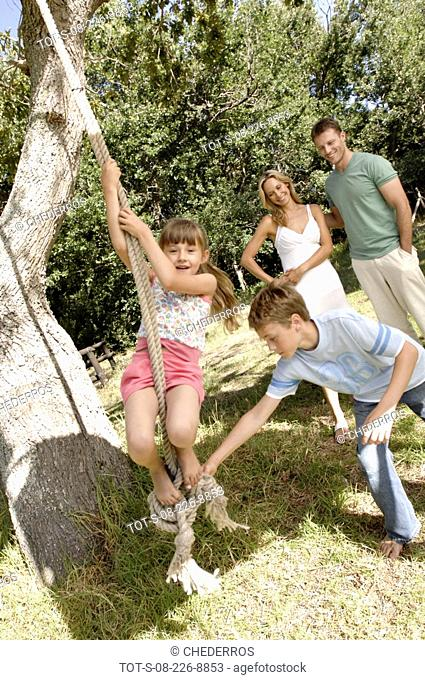 Boy swinging her sister on a rope swing with their parents smiling