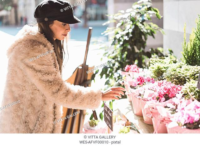 Stylish young woman buying flowers in the city