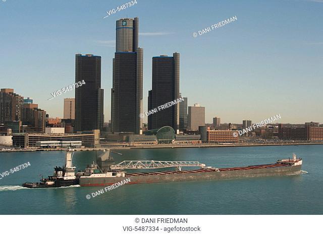 A large bulk carrier cargo ship travels along the Detroit River passing the Renaissance Center along the skyline of downtown Detroit, Michigan, USA