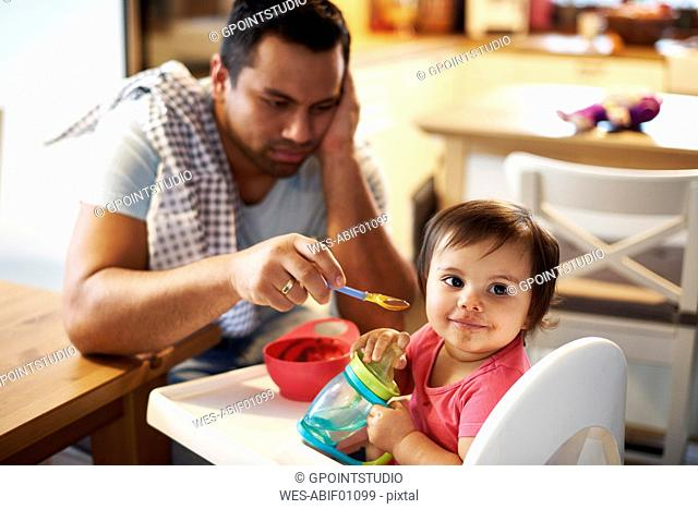 Portrait of baby girl sitting in high chair at home with annoyed father in background