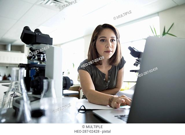 Focused college student using laptop near microscopes in science laboratory