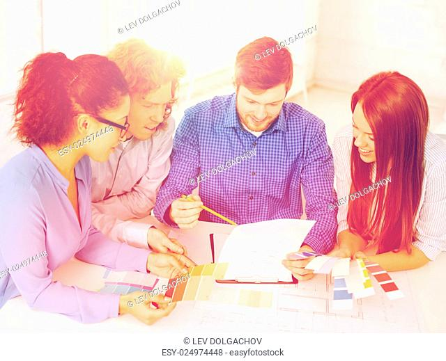 business, office, architecture and startup concept - smiling creative team with color samples and blueprint at office