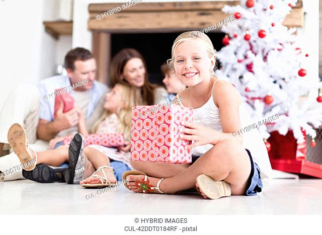 Girl sitting with wrapped Christmas gift