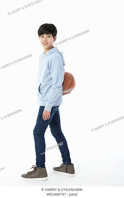 Side view of smiling school boy with a basketball standing staring at front