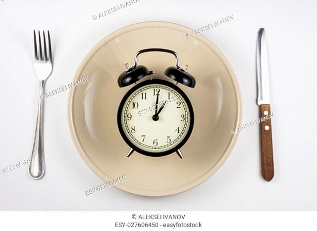 On the plate is an alarm clock, lying next to a knife and fork, white background, top view