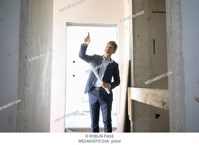 Architect with blueprint pointing his finger in building under construction