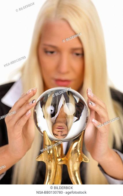 Young woman reads the future from a crystal ball in her hands