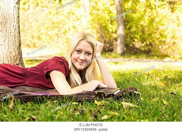 A young woman with long blond hair doing homework outdoors while enjoying a warm autumn day in a park and posing for the camera; Edmonton, Alberta, Canada