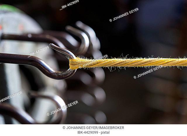 Passementerie, silk threads on hook of cord twisting wheel, third work step to make twisted cord, Munich, Bavaria, Germany