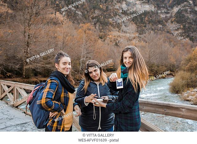 Spain, portrait of three young women with instant photos on a bridge in Ordesa National Park