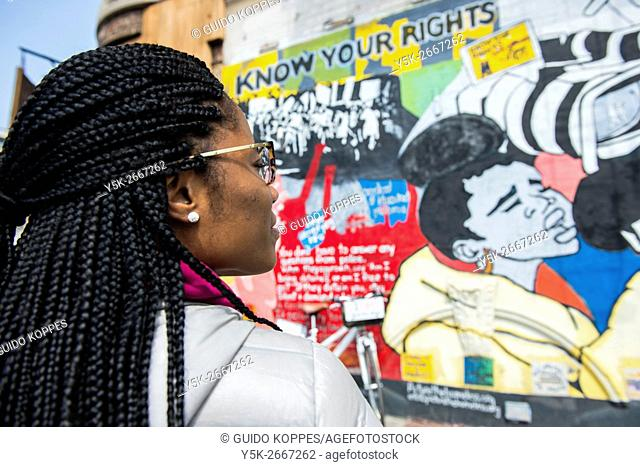 New York City, USA. Attractive African-American woman looking at a graffiti about civil rights on a building's wall, somewhere in Harlem, Manhattan