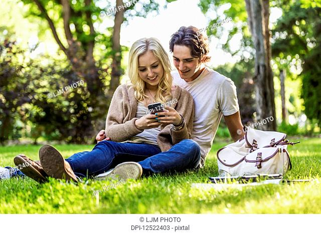 A young couple sits studying on the grass on the university campus with a textbook and tablet while using a smart phone; Edmonton, Alberta, Canada