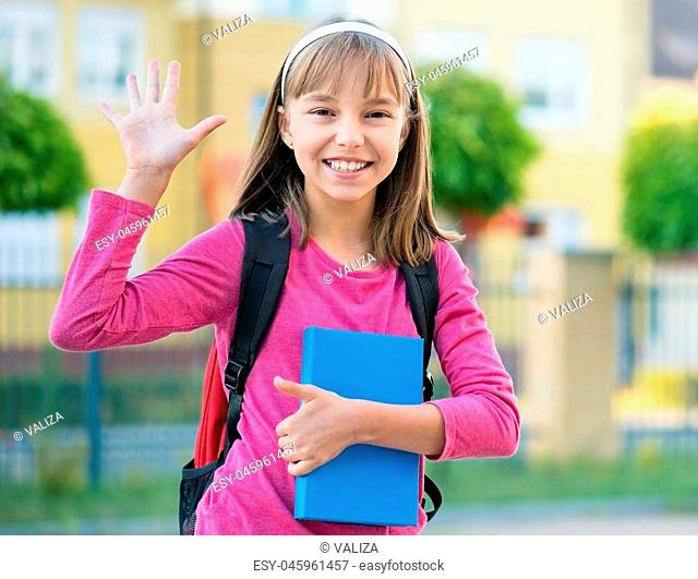 Outdoor portrait of happy child 10-11 year old with book and backpack. Girl stretching her right hand up for greeting. Back to school concept