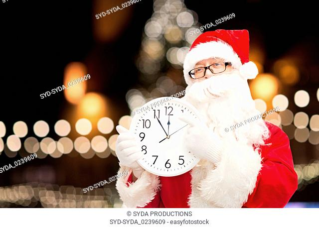 santa claus with clock pointing finger to twelve