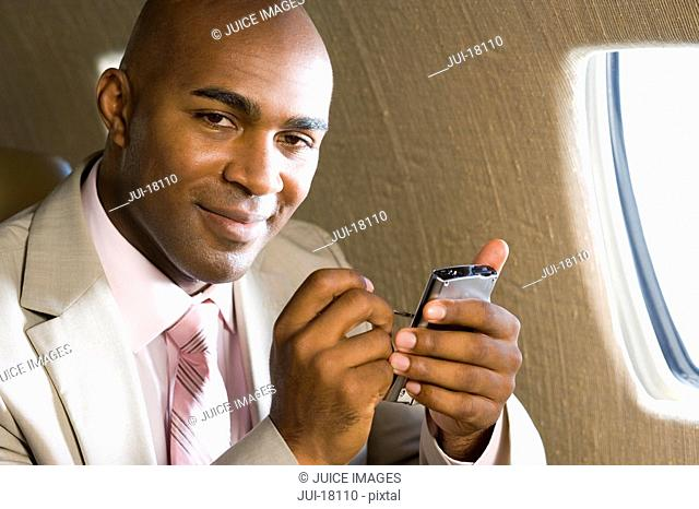 Businessman using mobile phone on aeroplane, portrait, close-up