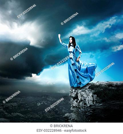 Full Length Photo of Fantasy Woman in Waving Blue Dress Reaching for the Light. Dramatic Moody Sky. HDR Cloudscape