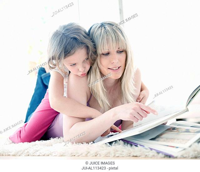 Young girl reading with mother on rug
