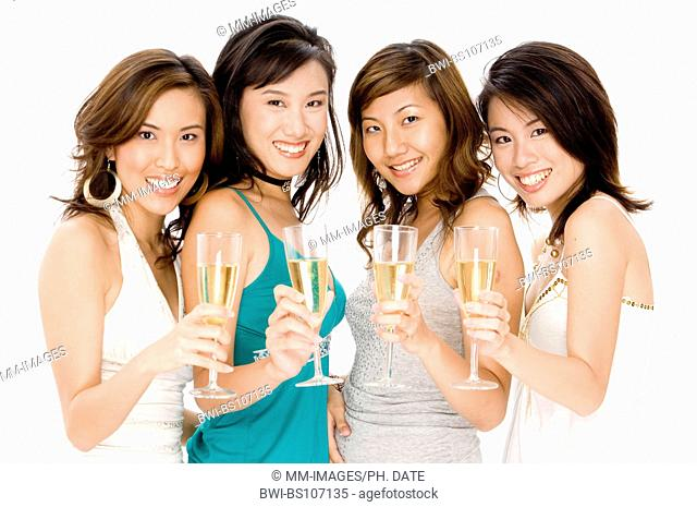 Four pretty young Asian women drinking glasses of champagne