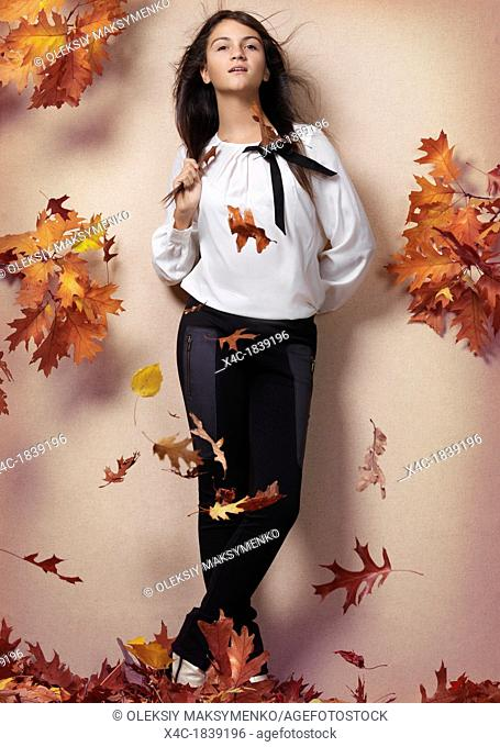 Teenage girl and red autumn leaves beautiful artistic fall fashion concept photo