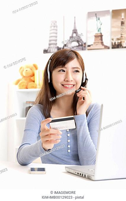 Young woman holding credit card and wearing headphones with smile