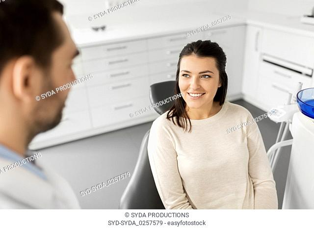 female patient talking to dentist at dental clinic