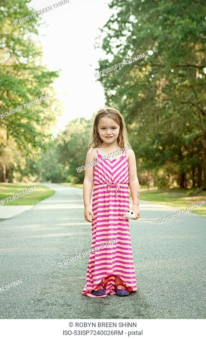 Smiling girl standing on rural road