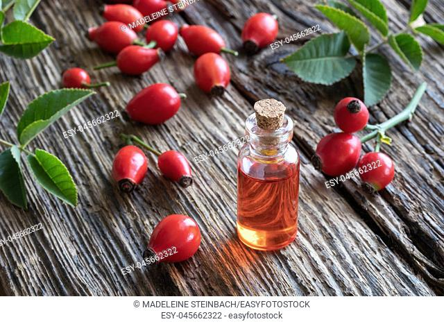 A bottle of rosehip seed oil with fresh berries