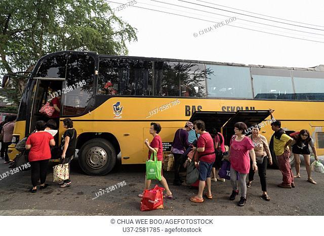 Taiqi members embarking a chartered school bus going to Lundu for picnic