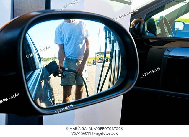 Man holding gas pistol, refuelling at a gas station