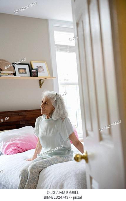Older woman sitting on bed beyond doorway