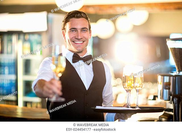 Portrait of smiling waiter offering a glass of champagne