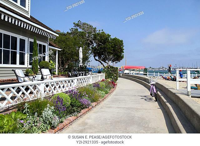 Sidewalk between homes and the beach on Balboa Island, Newport Beach, Orange County, California, United States