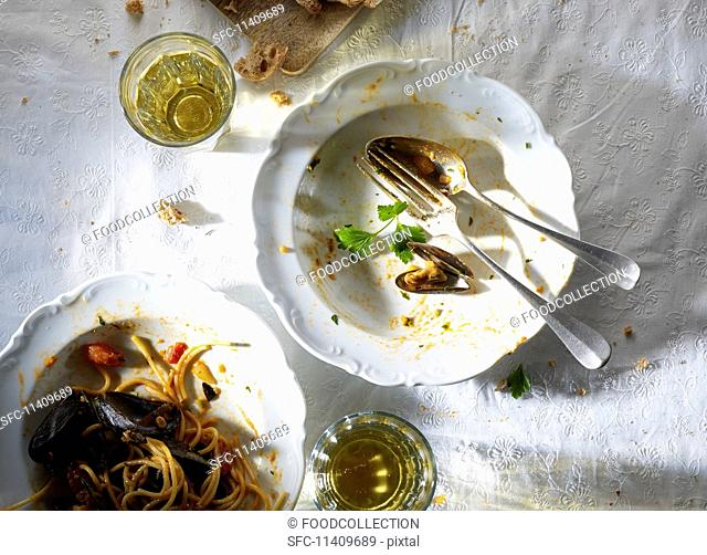 A plate with the remains of spaghetti and mussels